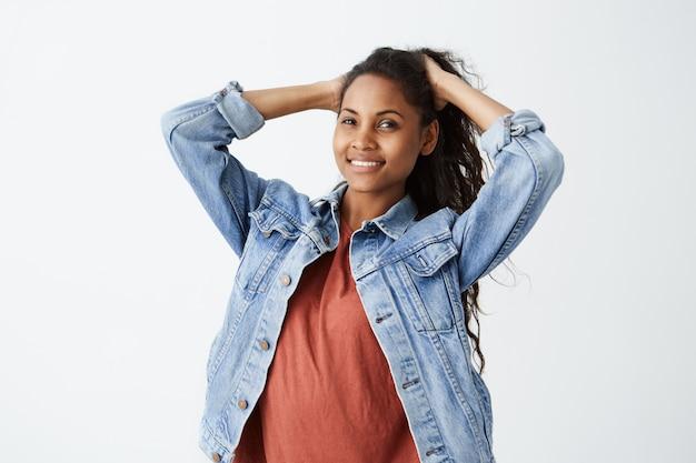 Стильная темнокожая девочка-подросток с волнистыми волосами и веселой улыбкой. красивая молодая женщина в джинсовой куртке и красной футболке подметает ее волосы, изолированные на белом.