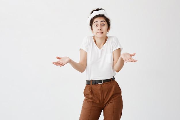 Невежественная девушка с темными волосами в пучке жестикулирует в замешательстве, так как не знает ответа на спорный вопрос. нерешительная молодая женская модель пожимает плечами в недоумении. концепция языка тела