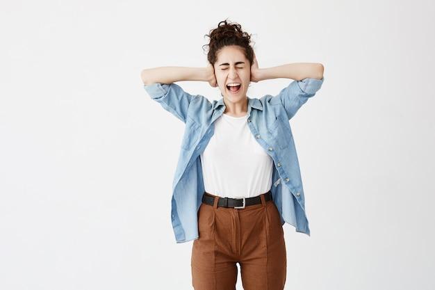 Девушка с темными волосами в булочке, носит джинсовую рубашку и коричневые брюки, затыкает уши руками, гримасничает, не хочет слышать сплетни. злая самка не выносит громкого звука, кричит с закрытыми глазами