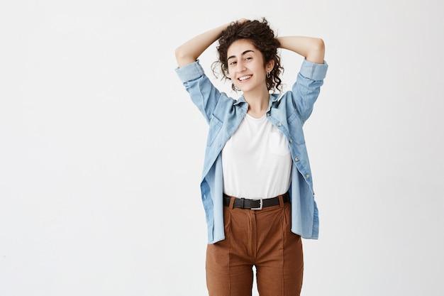 Концепция молодости и счастья. талия-вверх портрет красивая брюнетка девушка в джинсовой рубашке, глядя, улыбаясь, играя с ее длинными волнистыми волосами.