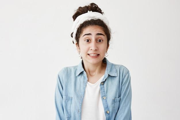 暗いウェーブのかかった髪とボロボロの緊張感、問題に直面しているときのストレス、ストレスに耐えられない、白い歯を食いしばるストレスのあるカジュアルな服装の女性。顔の表情、感情、感情