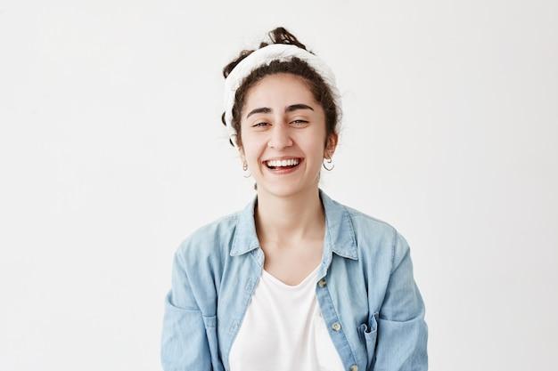 暗い髪の前向きな少女は、ドラグとデニムのシャツを着て、幸せそうに見え、広く笑い、冗談を笑い、若者を喜ばせます。白い壁に対して女性モデルのポーズ