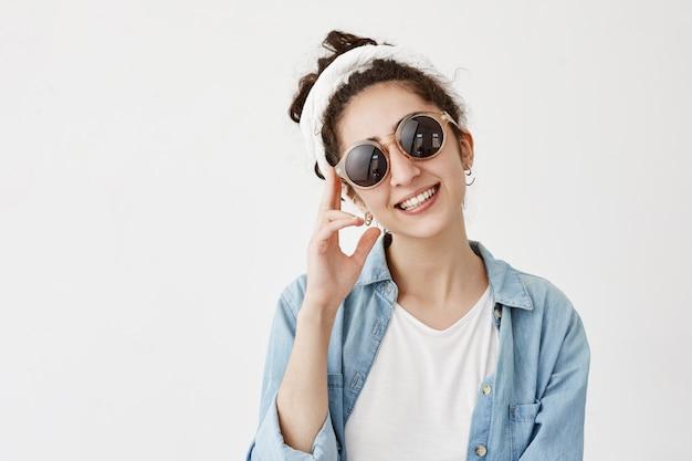 トレンディな丸いサングラスをかけたポジティブな女性モデルを笑顔でデニムシャツにドラグで、気分がよく、白い歯を見せ、友人や親戚に会えてうれしい。幸福、顔の表情のコンセプト