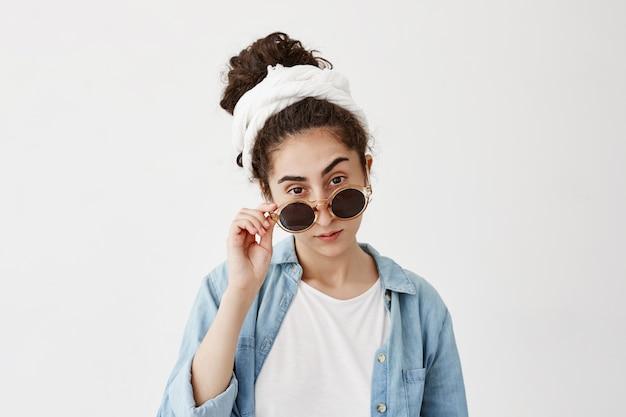 白いドラグとサングラスをかけた気取らない黒髪の女の子は、白い壁にポーズをとって、デニムシャツを着た魅力的なルックスです。顔の表現の広告ボディ言語のコンセプト。