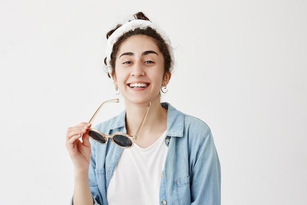 ドラグの笑顔でうれしそうな黒髪の女子学生は、デニムシャツに身を包んだ白い均等な歯を示し、コピースペースのある白い壁に対して屋内でリラックスして素晴らしい一日を過ごします。