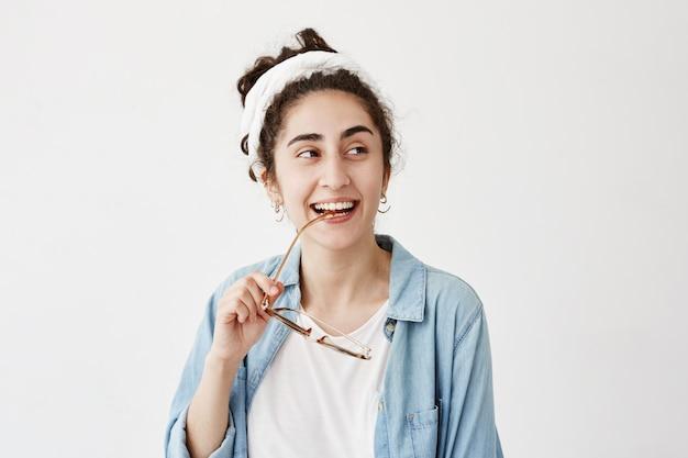 Счастливая улыбающаяся темноволосая женщина в до-тряпке в джинсовой рубашке, с очками, имеет хорошее настроение после получения хороших новостей, рада встрече с друзьями и родственниками. люди, счастье, концепция выражения лица