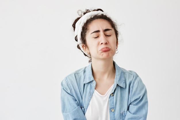悪い知らせを受け取った後、暗くてウェーブのかかった髪を持つ悲惨な動揺の憂鬱な女性は気分を害し、唇をふくれっ面にして、眉をひそめ、失望している。デニムシャツの不幸な若い女の子は欲求不満で泣く