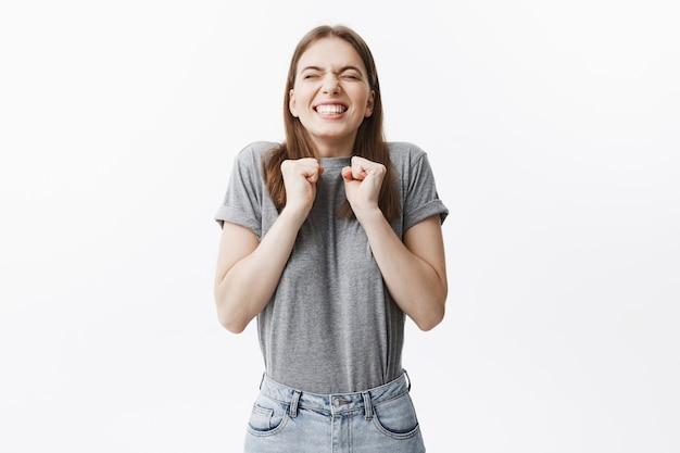 Мне так везет. портрет красивого жизнерадостного европейского молодого студента сжимает руки перед комодом с закрытыми глазами и яркой улыбкой, зная, что она выиграла в художественном конкурсе.