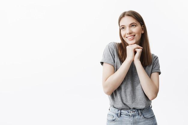 Крупным планом очаровательная красивая молодая студентка с темными волосами и глазами в повседневной одежде улыбается, смотрит в сторону с мечтательным и счастливым выражением лица, держась за руки под лицом