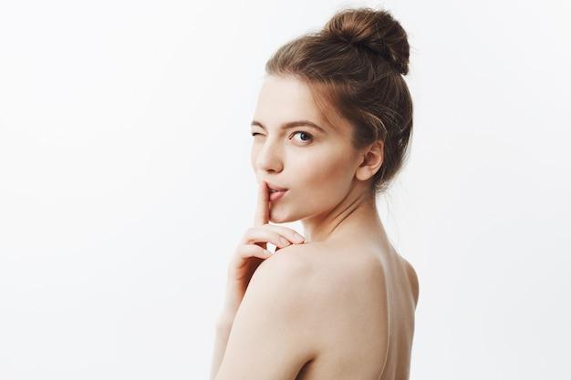 お団子の髪型と裸の肌に黒い長い髪を持つ魅力的な美しい若いヨーロッパ女性の肖像画を間近します。まばたき、静けさのジェスチャーで人差し指で唇に触れる