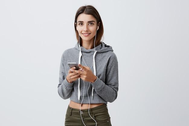Позитивные эмоции. портрет красивой сногсшибательной темноволосой кавказской девушки в модном сером наряде по дороге в университет, слушая музыку в наушниках, просматривая временную шкалу в соц.