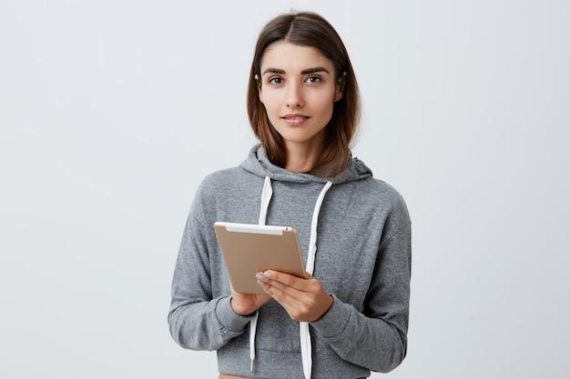 Крупным планом портрет красивой очаровательной молодой кавказской женщины с коричневыми длинными волосами в повседневной стильной одежде нежно улыбаясь, держа в руках цифровой планшет