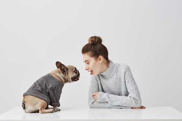 Милая женщина с прическа моды и ее щенка французский бульдог, одетый в перемычку. женская модель сидя на таблице с собакой над белой стеной. концепция дружбы, копия пространства