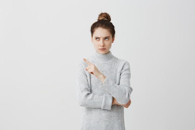 Сконцентрированная женщина смотря к стороне и показывая с указательным пальцем. женщина с волосами в булочке, имеющая строгое выражение лица, хмурящееся выражение, не любит это.