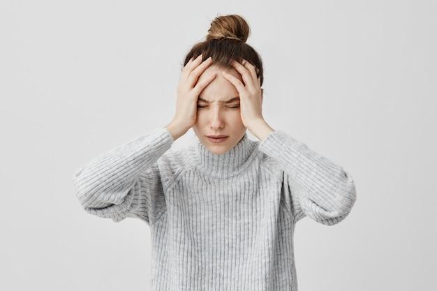 目を閉じて頭に触れて疲れきった若い女性。耐え難い頭痛に苦しんでいる女性の交換労働者。健康の概念