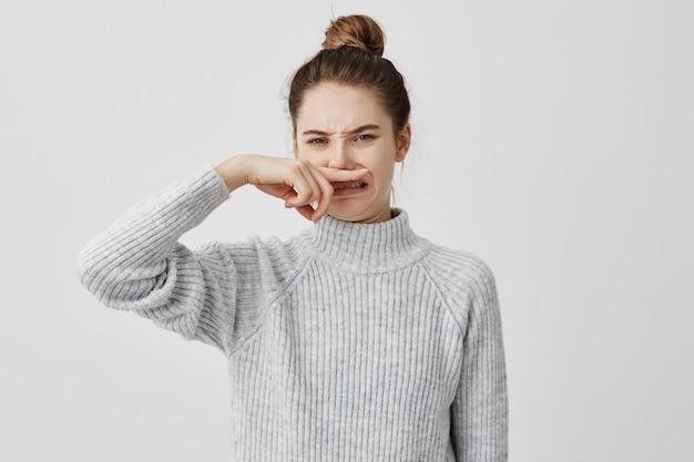 人差し指で嫌悪感を持って見ているカジュアルな閉じた鼻を着ている不快な女性。カフェでの作業中に不快な臭いがする若い女性ブロガー。悪臭のコンセプト