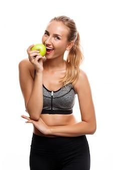 Красивая спортивная женщина позирует, держа яблоко