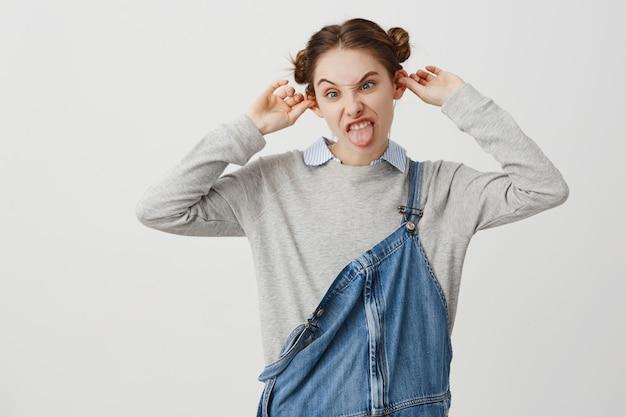 耳を突き出してゆがめるデニムジャンプスーツを着て変な格好の女性。トレンディなヘアスタイルが狂って浮気している生意気な女性反逆者。メリット、楽しいコンセプト