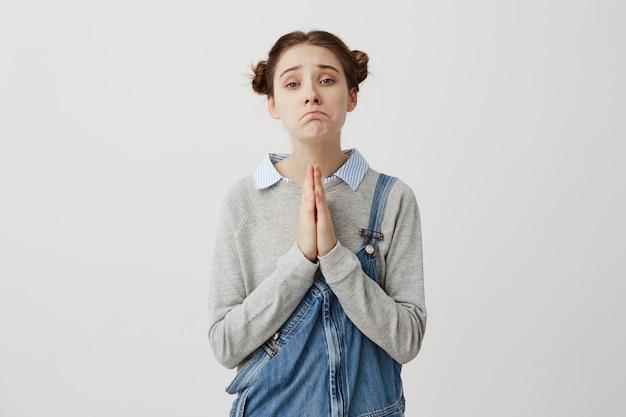 Женщина с каштановыми волосами в двойных булочках, позирующих с жалким взглядом, держащим руки в молитве. жалкие эмоции девушки, просящей прощения над белой стеной. понятие эмоций
