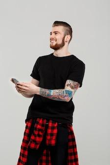 灰色の壁を越えて携帯電話を保持している若いハンサムな男。
