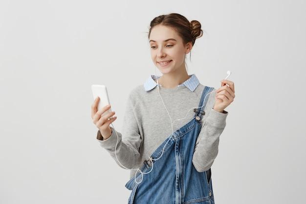 Красивая дама в джинсовых комбинезонах, глядя на ее телефон широко улыбается. современная дружелюбная жена разговаривает по скайпу с мужем, находясь в командировке. концепция связи