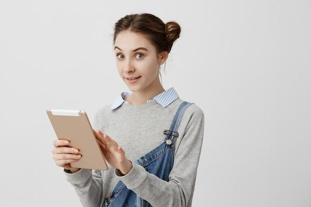 ノートブックを保持している喜んでの視線で探しているおだんごパンで女の子らしい白人女性。新しいデジタルタブレットをテストする女性のバイヤーの肯定的な感情。テクノロジー、未来