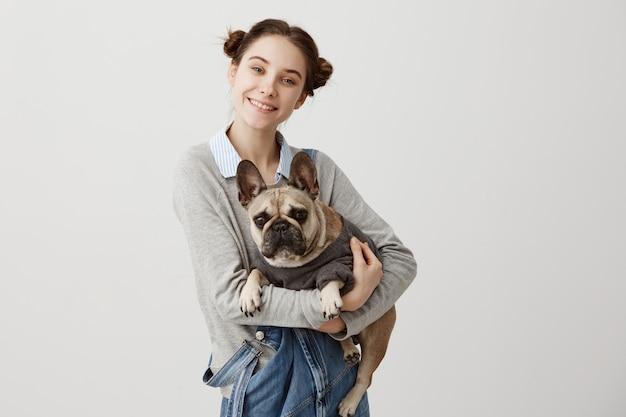 Кавказская женщина и ее любимец с улыбкой. жизнерадостный женский фотограф фотографируя и родословная собака лежа в ее руках. концепция дружбы
