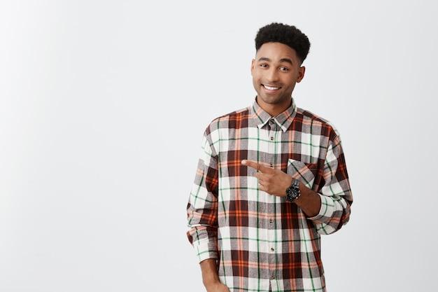Скопируйте место для рекламы. темнокожий молодой симпатичный радостный мужчина с кудрявой прической в клетчатой рубашке, указывая одной рукой с улыбкой и счастливым выражением лица.