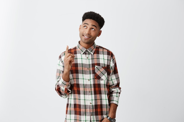 Портрет молодого темнокожего африканского привлекательного человека с вьющейся прической в повседневной клетчатой рубашке, указывающей вверх ногами с счастливым и расслабленным выражением. копировать пространство