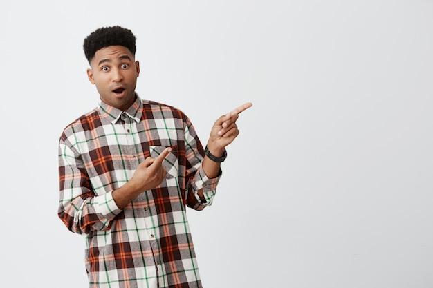 Крупным планом изолированных портрет красивой молодой темнокожий африканский студент парень с модной рубашке, указывая в сторону на белой стене с раскрытой пасти и удивленным выражением