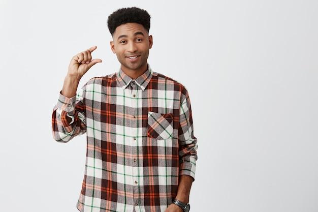 若干。皮肉な表情で手で身振りで示す、市松模様のシャツを着た笑顔でアフロのヘアカットをした若いハンサムな黒肌の面白い男の肖像。