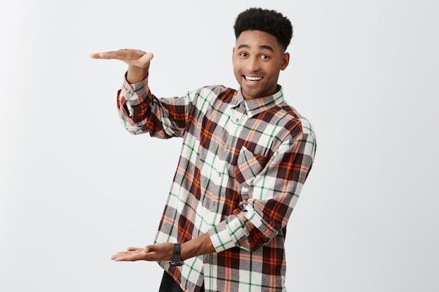 Веселый зрелый чернокожий парень с афро прической в повседневной клетчатой рубашке, жестикулирующей руками, делает вид, что держит большую коробку со счастливым выражением лица.