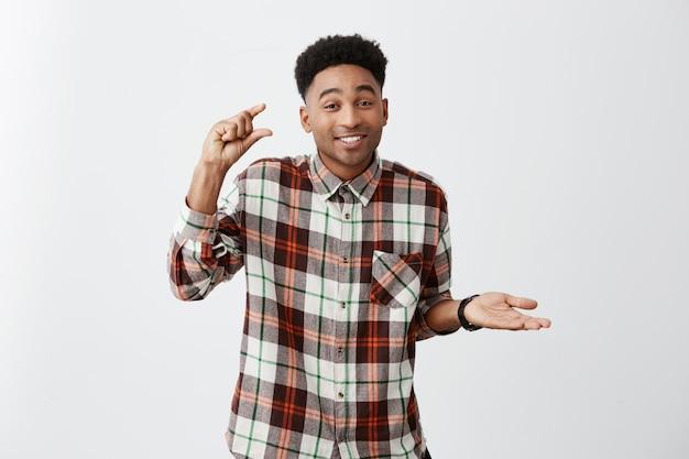 Закройте вверх по портрету смуглого темнокожего молодого человека с афро прической в вскользь рубашке жестикулируя рукой, держа свободное пространство с пальцами с саркастическим выражением лица.