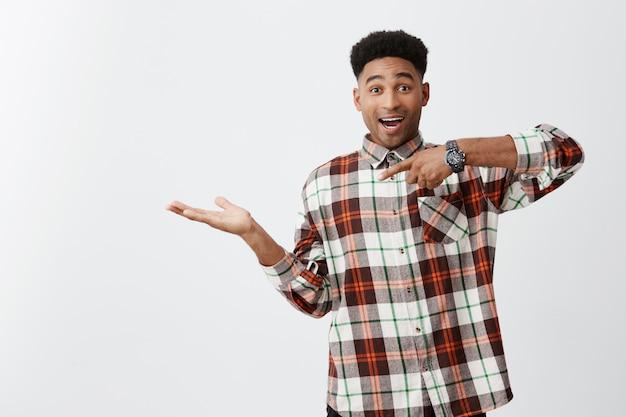 Портрет молодого веселого темнокожего забавного парня с афро прической в клетчатой повседневной рубашке, притворяющейся держащей что-то на ладони, указывающей на нее рукой с волнующим выражением