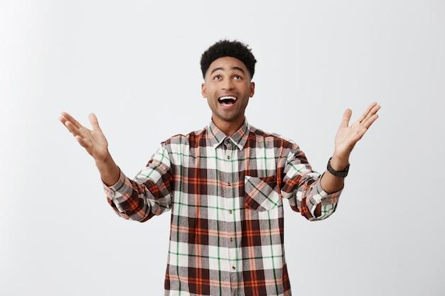 Слава богу. возбужденный молодой темнокожий ученик с вьющимися волосами в клетчатой рубашке, раскинув руки, смотрит вверх ногами с раскрытым ртом, чувствуя себя супер счастливым, чтобы сдать тяжелый экзамен в университете.