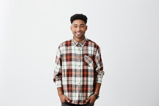Изолированные на белой стене. люди и эмоции. молодой красивый темнокожий мужчина улыбается, носить клетчатую рубашку с счастливым и расслабленным выражением лица.
