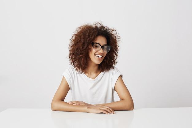 Красивая африканская девушка в стеклах смеясь над сидеть над белой стеной. копировать пространство