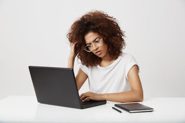 Утомленный и уверенный молодой африканский студент дизайна моды думая на ее исследовании работая на компьтер-книжке на бизнес-плане будущего бренда. выдающийся сценарист в ее двадцатых на белой стене.