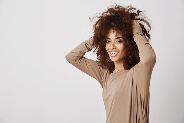 彼女の髪に触れて笑って幸せな美しいアフリカの女の子。白い壁。