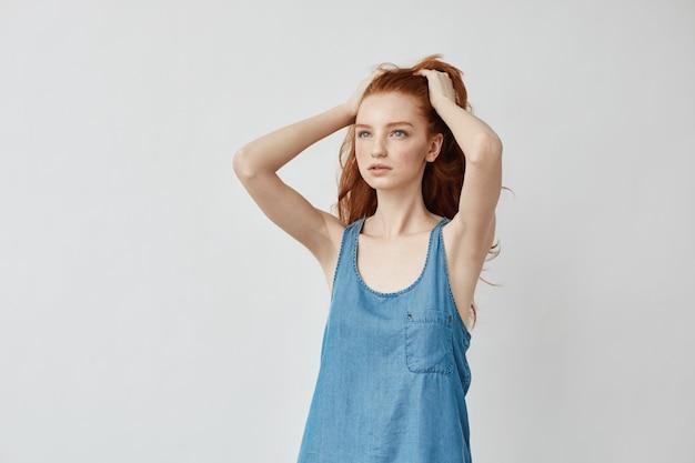距離を見てポーズをとって髪に触れる美しい赤毛のモデル。