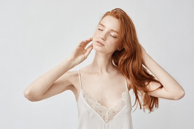 目を閉じてポーズをとって優しい裸赤毛モデル。