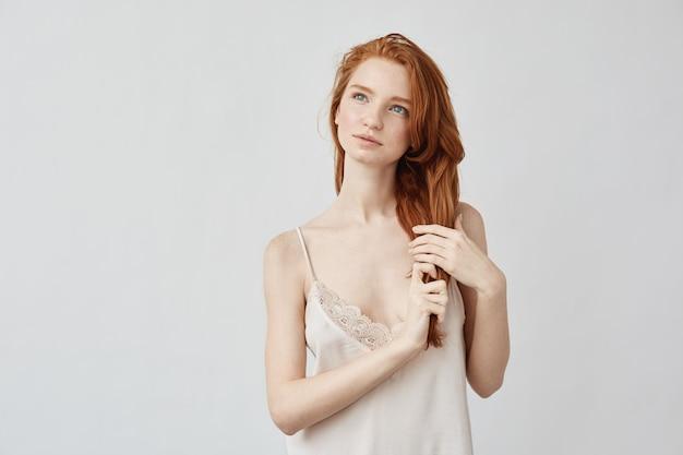 距離を夢見てパジャマで美しい生姜の女の子。