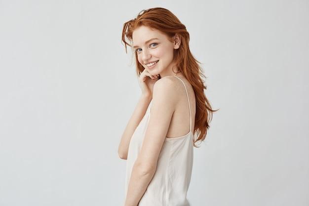 Красивая рыжая девушка с веснушками улыбается