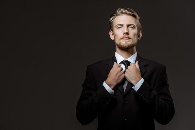 Молодой успешный бизнесмен, исправляя куртку