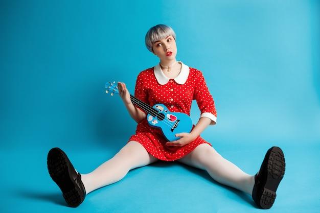 Крупным планом портрет красивой кукольной девушки с короткими светло-фиолетовыми волосами в красном платье, держащей гавайскую гитару над синей стеной