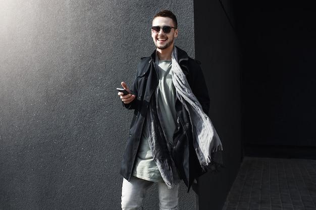 Молодой красивый парень в прохладный весенний наряд, стоя на улице.