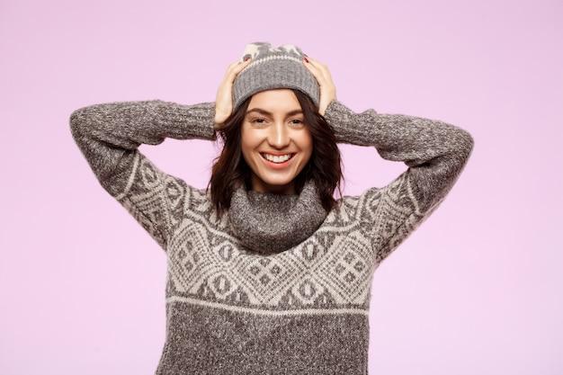 Молодая красивая девушка улыбается через светлую стену