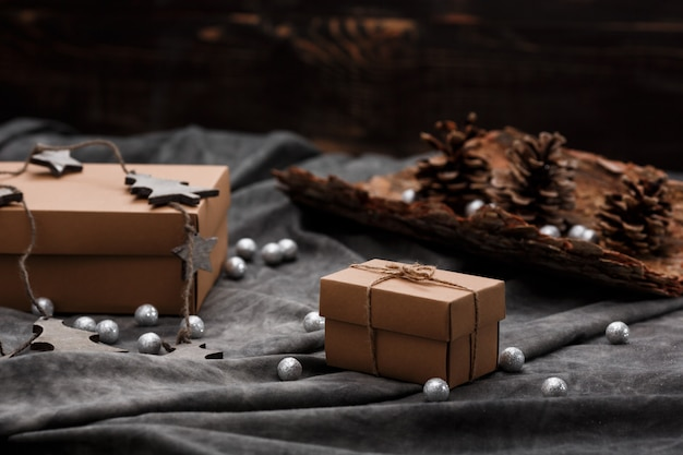 Новогоднее украшение и подарочные коробки на серой поверхности