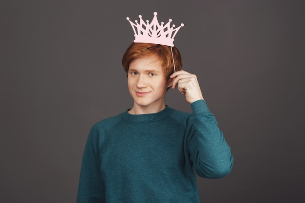 志望の王様。自信に満ちた表情で、スティックに紙の王冠を折りたたむスタイリッシュなグリーンのセーターで生姜の若いハンサムな男性のティーンエイジャーのクローズアップ。