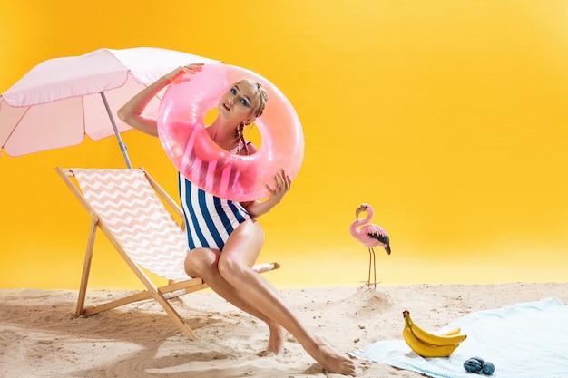 ビーチの衣装で素敵な若い女性はピンクの水泳リングを保持します